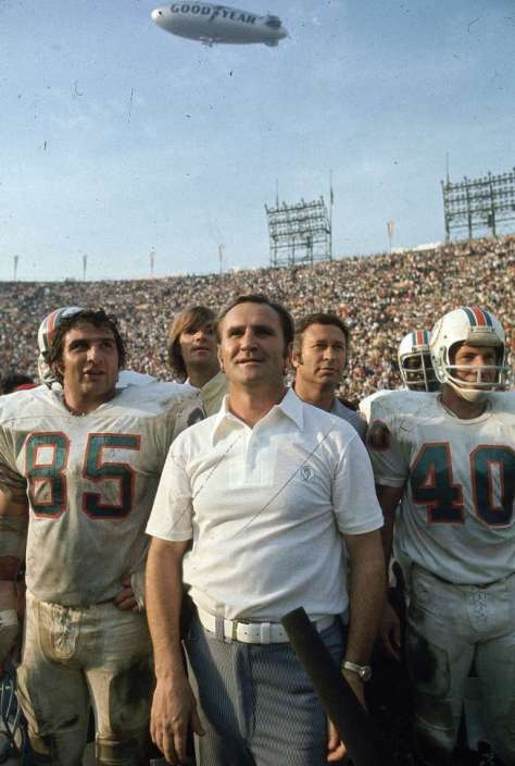 Miami Dolphins coach (C) with players after game vs Washington Redskins. . Dolphins go undefeated with 17 straight victories.