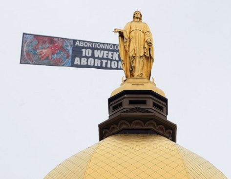 A banner towed by a small plane is seen flying past the Golden Dome and statue of the Virgin Mary at the University of Notre Dame campus in South Bend, Ind., on April 29. Anti-abortion activists have stepped up such displays in the weeks leading up to President Obama's planned address on campus Sunday. AP/South Bend Tribune